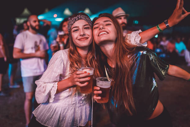two young women enjoying a night at the music festival - girls party zdjęcia i obrazy z banku zdjęć