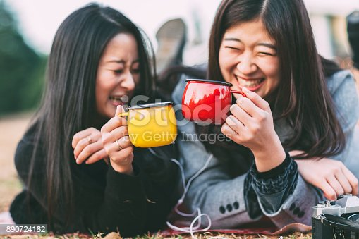 Two young Japanese women are enjoying hot drink and listening to music in a park in autumn.