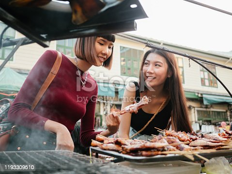 Happy asian girls buying chicken and port grill with her friend at Khao San Road in Bangkok, Thailand.