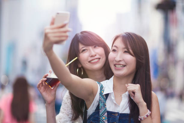 two young women enjoying taking selfie - self portrait photography stock pictures, royalty-free photos & images