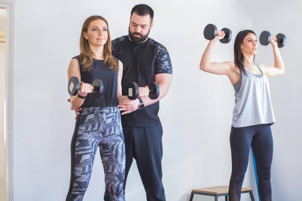dos mujeres jóvenes haciendo ejercicio en casa con entrenador personal - foto de stock