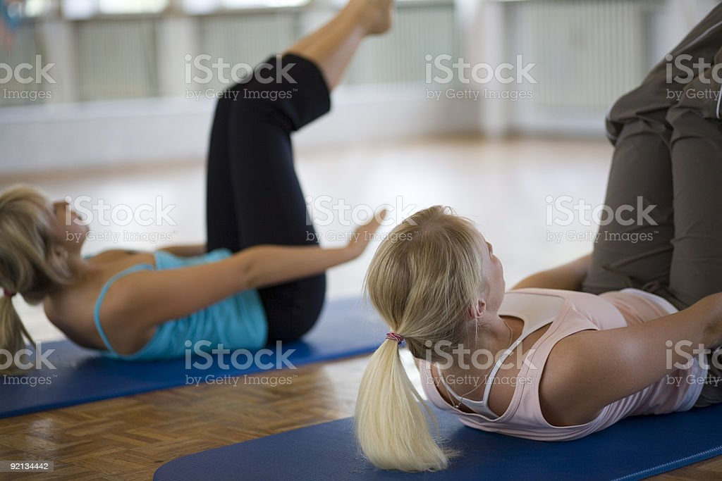 Two young women exercising on Pilates mats royalty-free stock photo