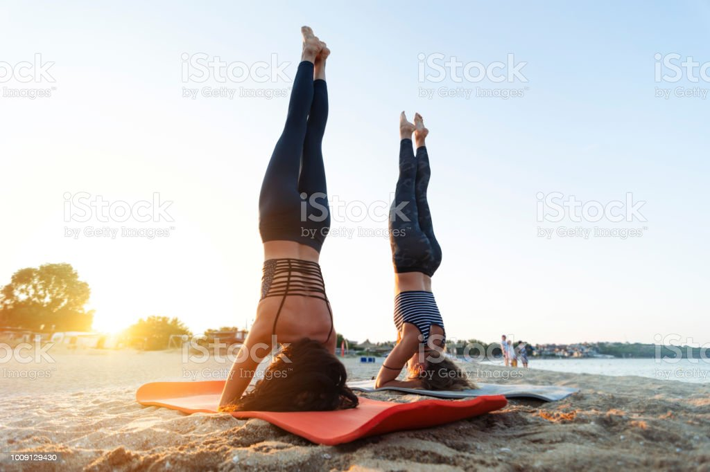 Two young women exercising on the beach zbiór zdjęć royalty-free