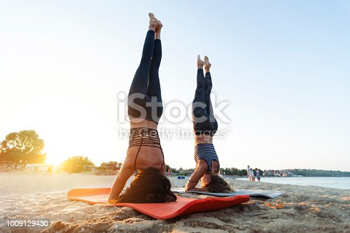 Two young women doing yoga outdoor on the beach in sunset time