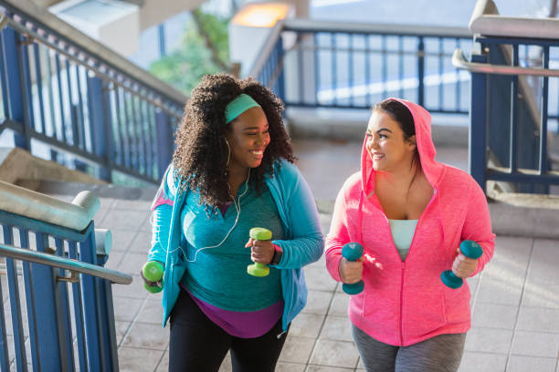Two young women exercising, powerwalking up stairs stock photo
