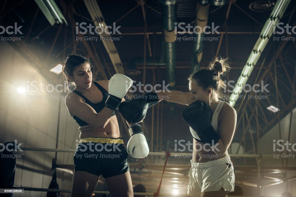 Muscular build women fighting on a kickboxing match in a health club.