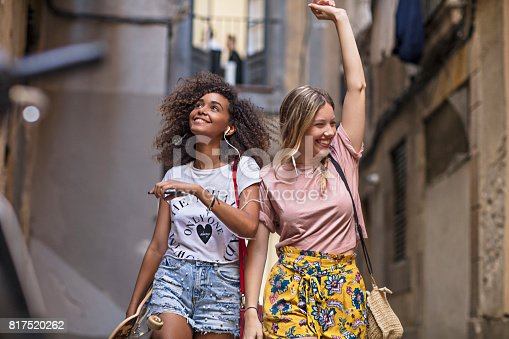 Two multi-ethnic young women friends having fun sharing music in the street.