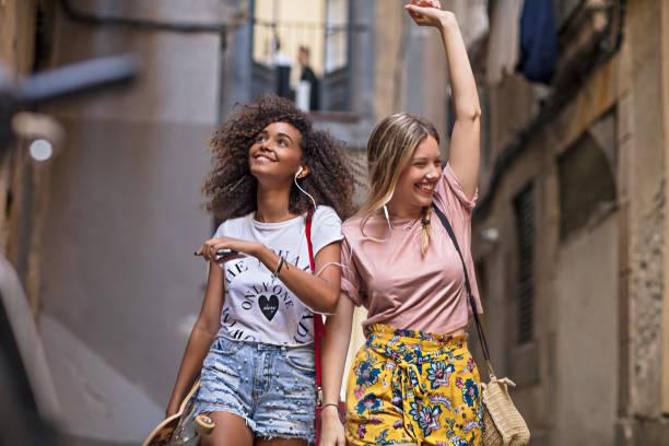 deux amis de jeunes femmes s'amuser partage de musique dans la rue - génération z photos et images de collection