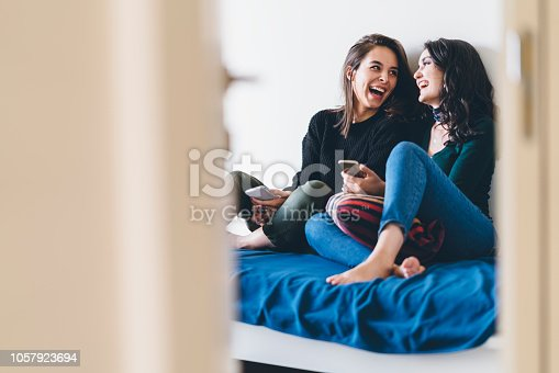 Two young women friends are talking and laughing happily at home.