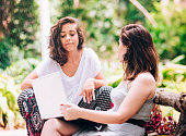Two young women friends using laptop outdoors