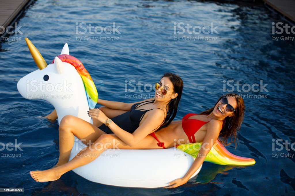 Two young women have fun in the pool stock photo