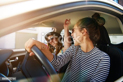 istock Two young women having fun driving along a street 699803744