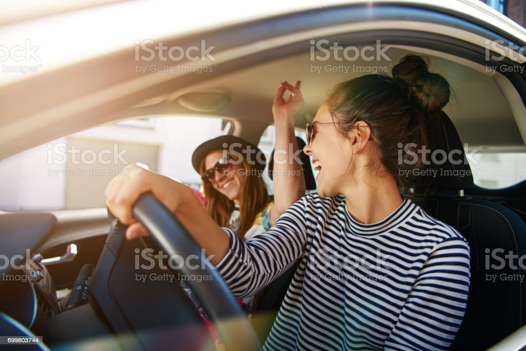 Two young women having fun driving along a street - foto stock