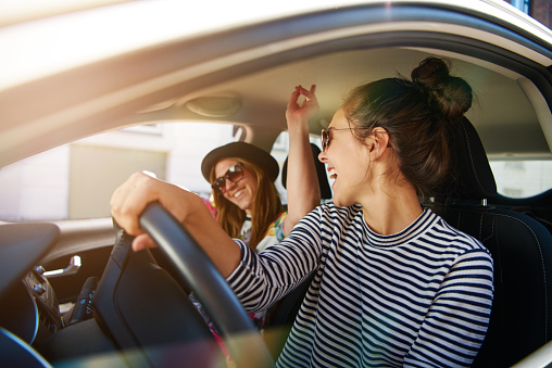 Two Young Women Having Fun Driving Along A Street Stock Photo - Download Image Now