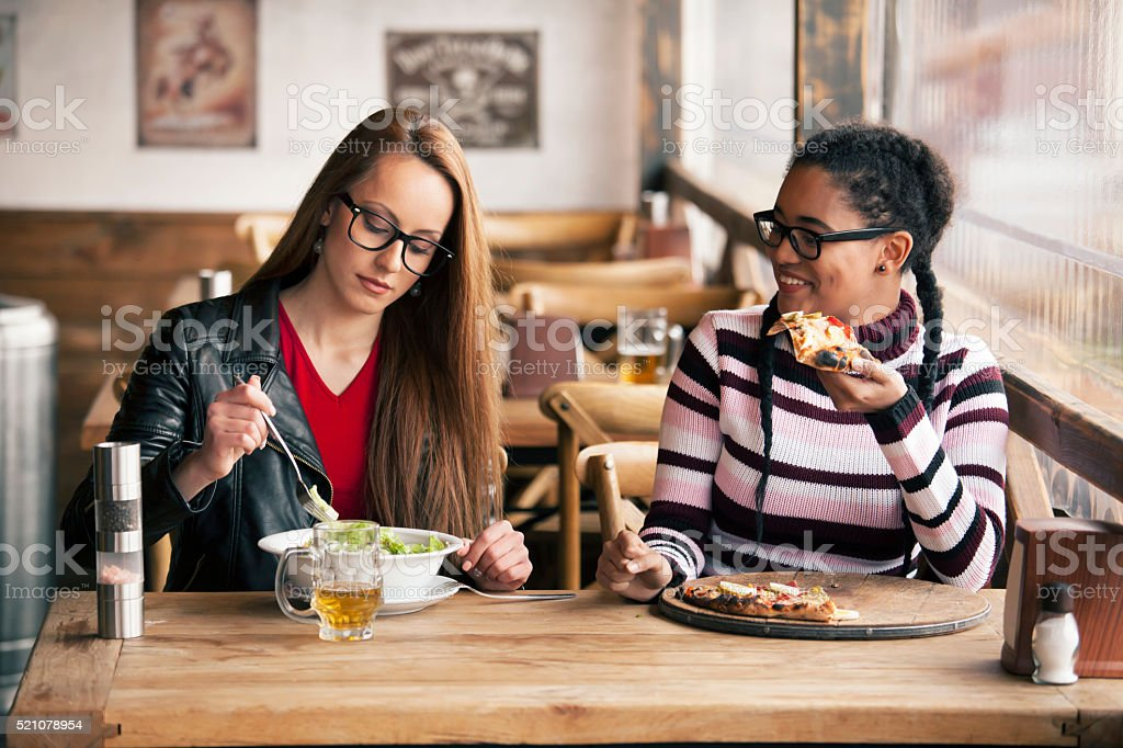 Two young women having lunch break at restaurant stock photo