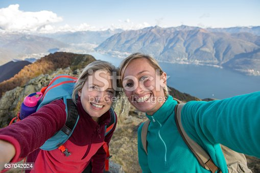 istock Two young women hiking take selfie portrait at mountain top 637042024