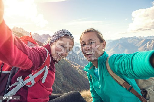 istock Two young women hiking take selfie portrait at mountain top 637191320