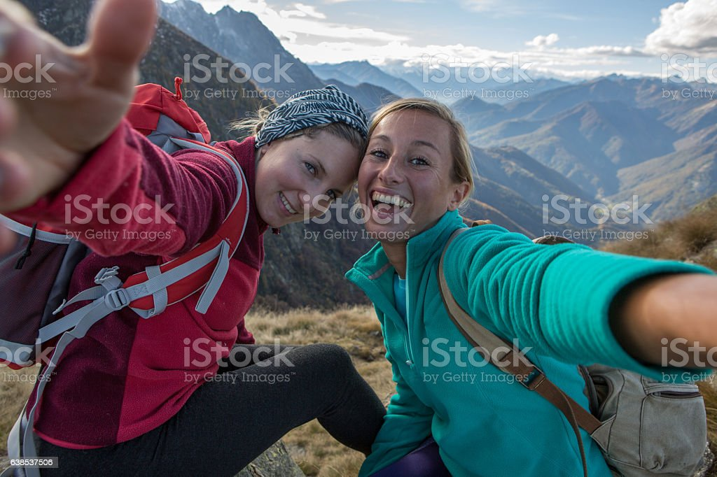 Two young women hiking take selfie portrait at mountain top Two young women hiking take a selfie portrait at the mountain top. Achievement Stock Photo