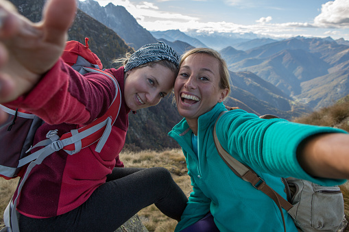 Two young women hiking take selfie portrait at mountain top