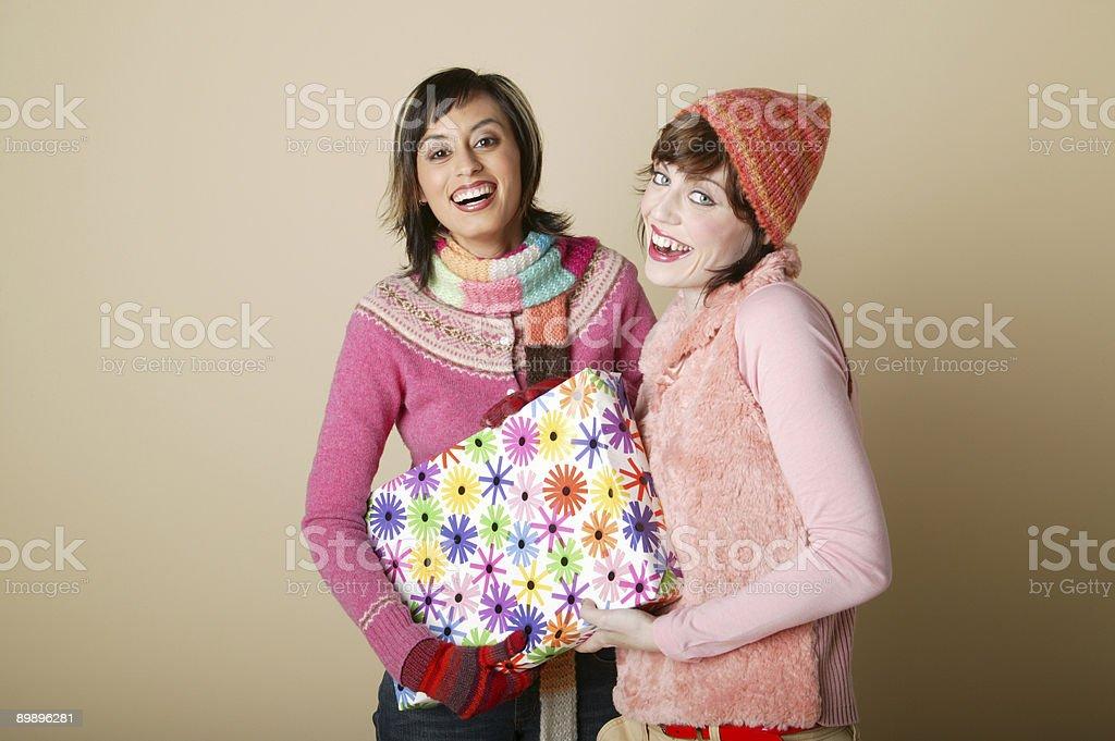 Две молодые женщины, держа подарок Стоковые фото Стоковая фотография