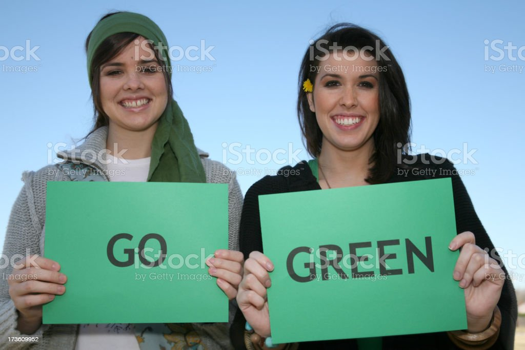 Two Young Women Holding Go Green Signs royalty-free stock photo