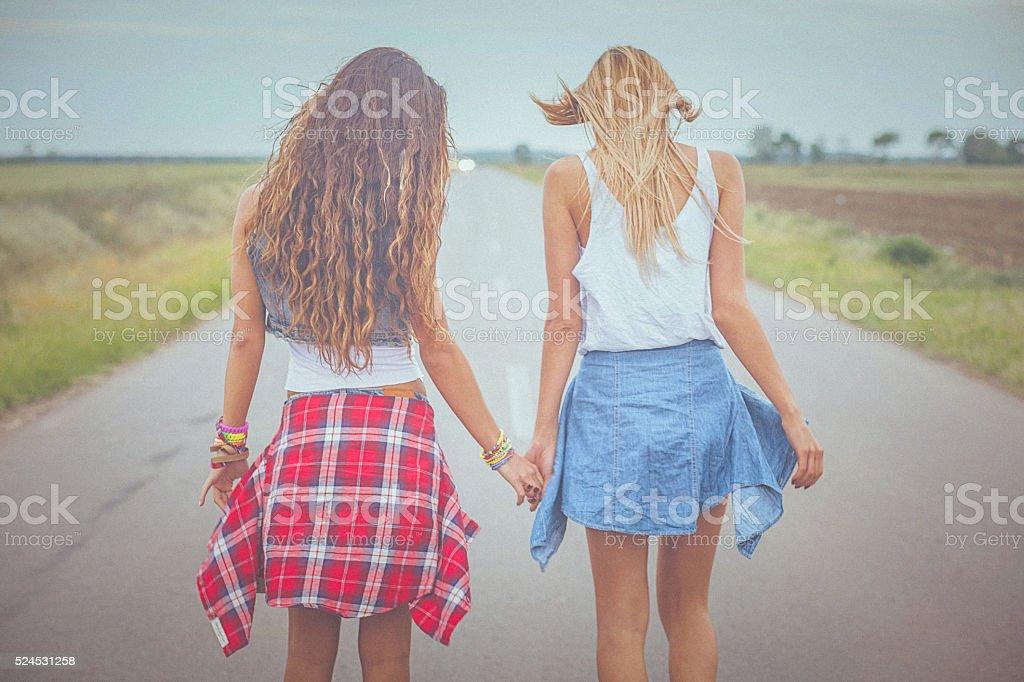 Deux jeunes femmes main dans la main et de marcher sur la route - Photo