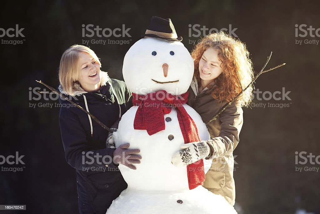 Two young women hugging snowman royalty-free stock photo