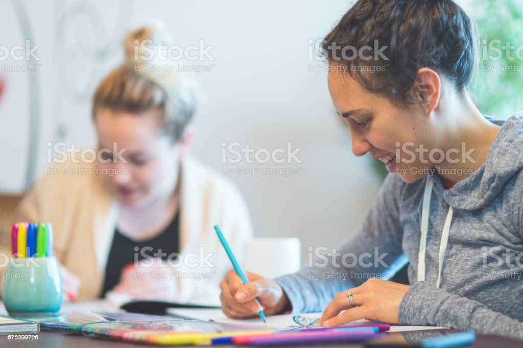 Two young women in 20s drawing in adult color coloring books together stock photo