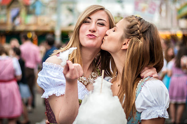 two young women in dirndl dress or tracht, kissing with - oktoberfest stock pictures, royalty-free photos & images