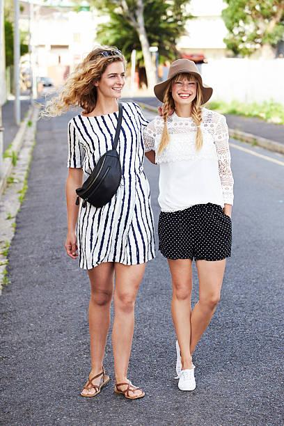 zwei junge frauen in modische kleidung, lächeln - lange gestreifte röcke stock-fotos und bilder