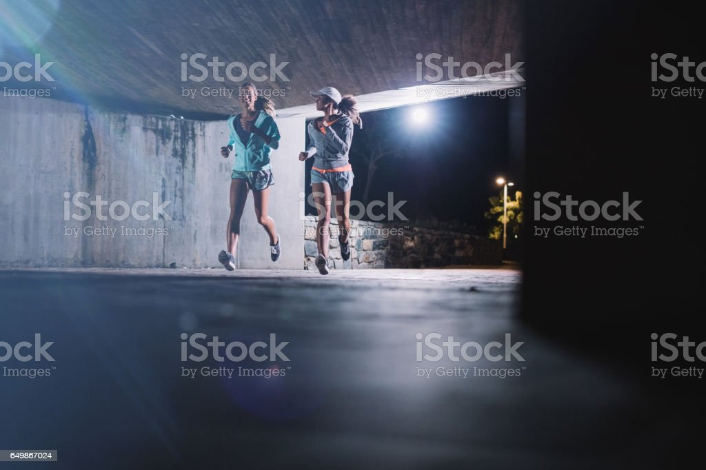 Two young women jogging at night in city – Foto