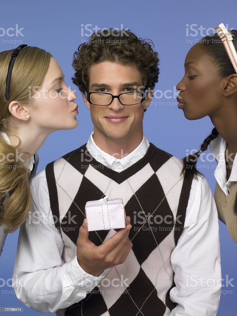 Two young women kissing a man royalty-free stock photo