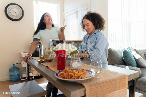 istock Two young women, Latino and African-American, roommates, talking in the kitchen of their rental apartment 1160296858