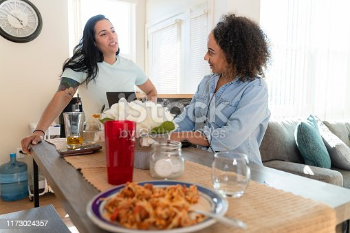 istock Two young women, Latino and African-American, roommates, talking in the kitchen of their rental apartment 1173024357