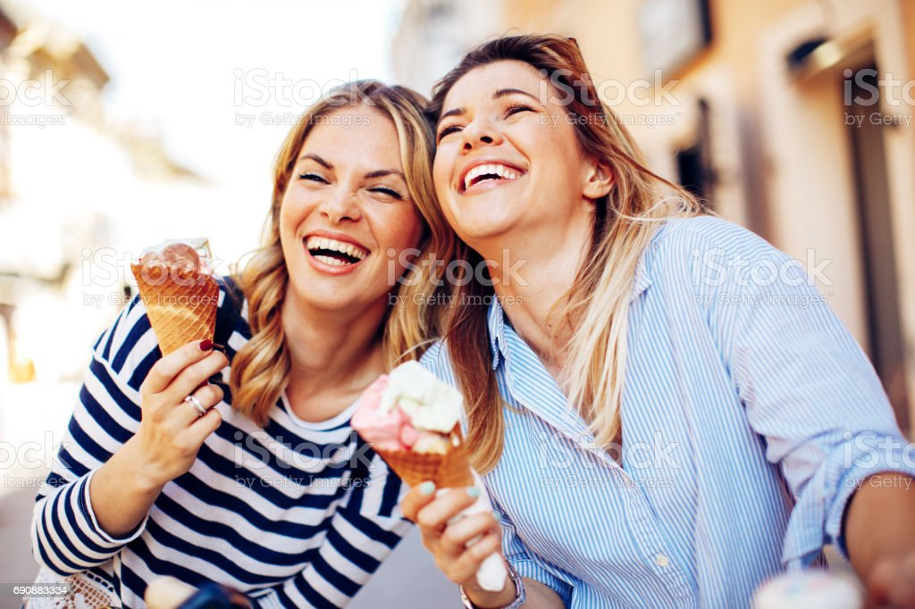 Two young women laughing and holding ice cream in hand stock photo