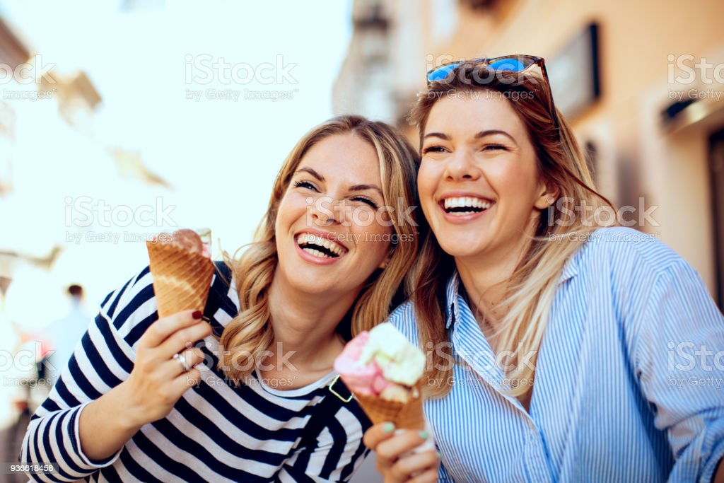 Two young women laughing and holding ice cream in hand royalty-free stock photo