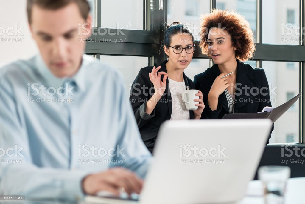 Two young women laughing behind their male colleague stock photo