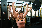 Two strong young women exercising in the gym and lifting weights