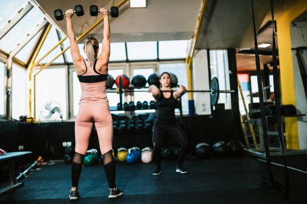 Two young women lifting weights in the gym stock photo