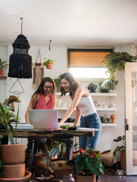 Two young women looking at laptop computer in workplace stock photo