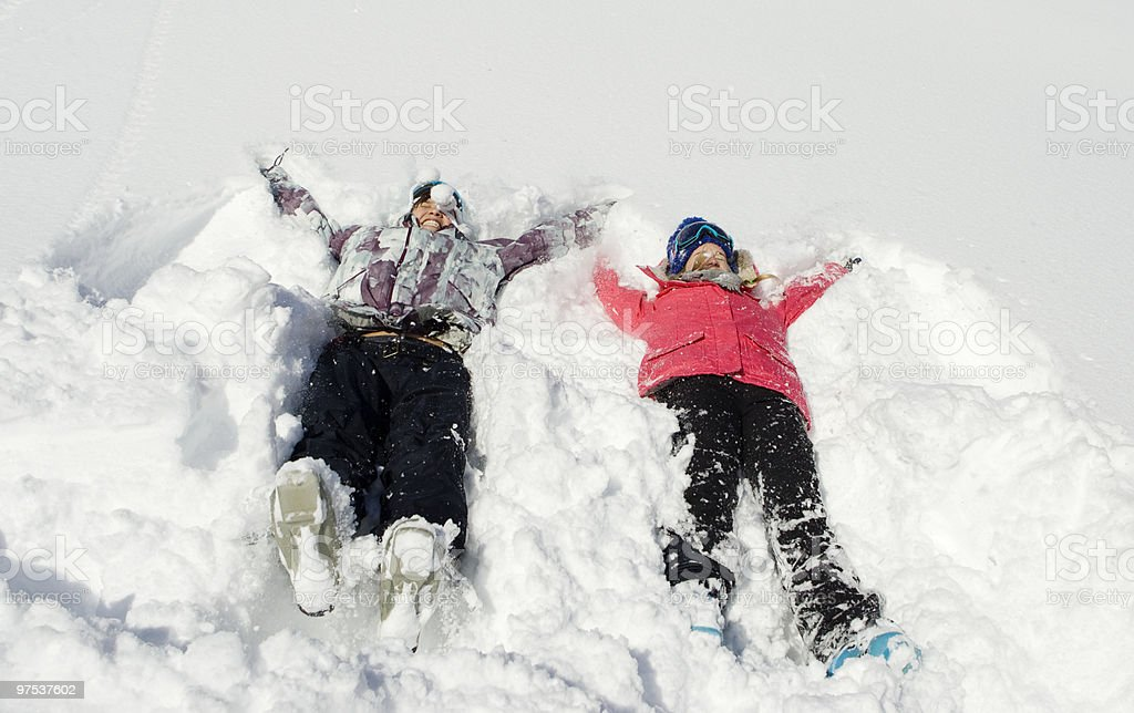 Two young women making snow angels. photo libre de droits