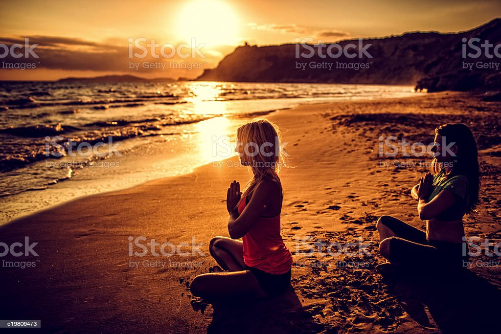 Two young women meditating in a fire log position stock photo