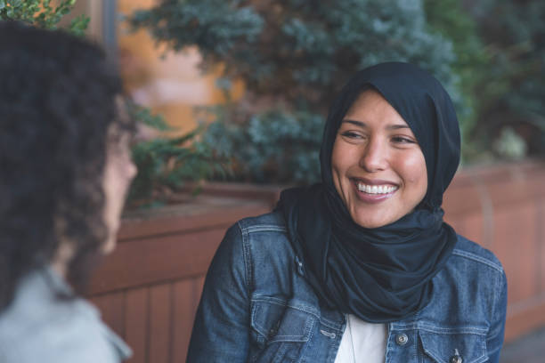 Two young women of Middle Eastern descent talking in the city stock photo