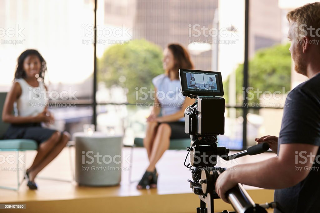 Two young women on set for TV interview, focus on foreground - foto de stock