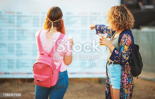 Two young women standing in front of the beer fest time table billboard and pointing at event