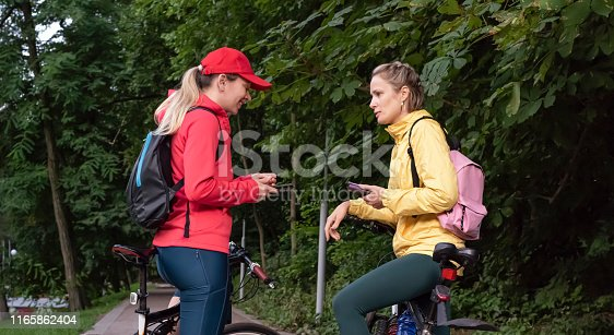 Two young women in sports clothing on the bike in the city park collate the route on a map on your phone.