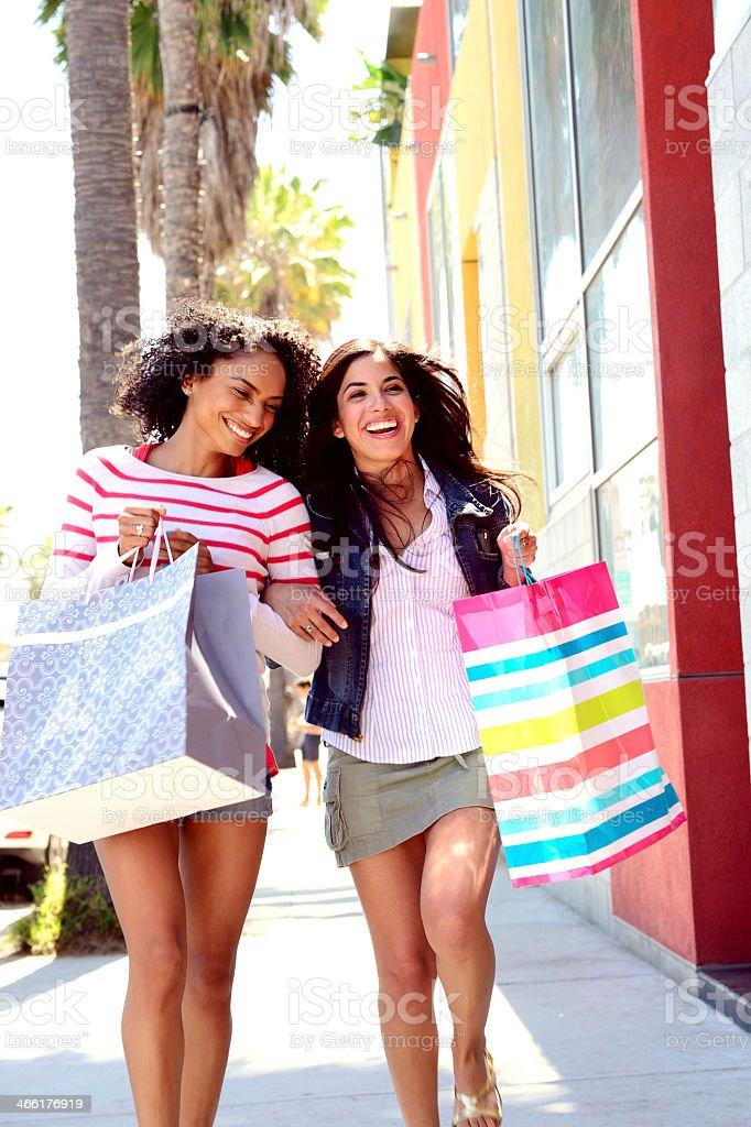 Two young women out shopping, having fun stock photo