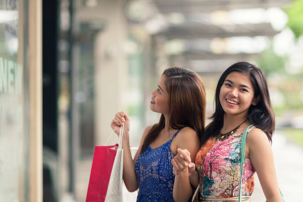 two young women out shopping - philippines girl stock photos and pictures