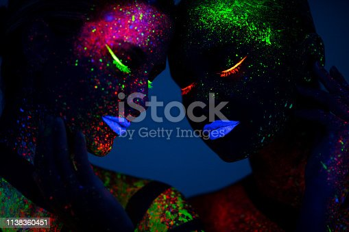 Two young women painted with fluorescent colors standing in front of ultraviolet light. Space is dark with blue background.