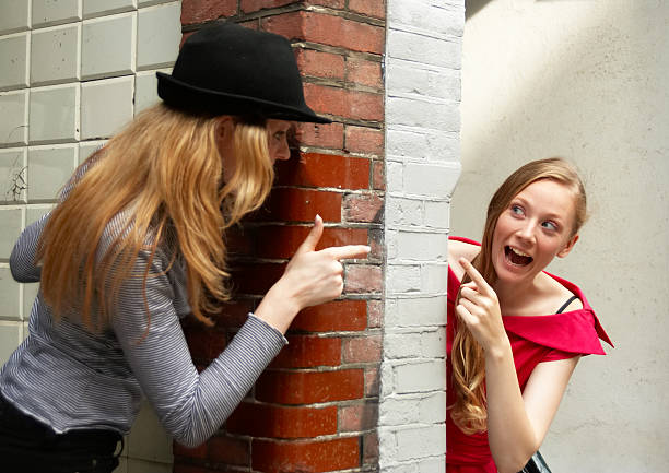 Two young women peeking round a wall at each other stock photo